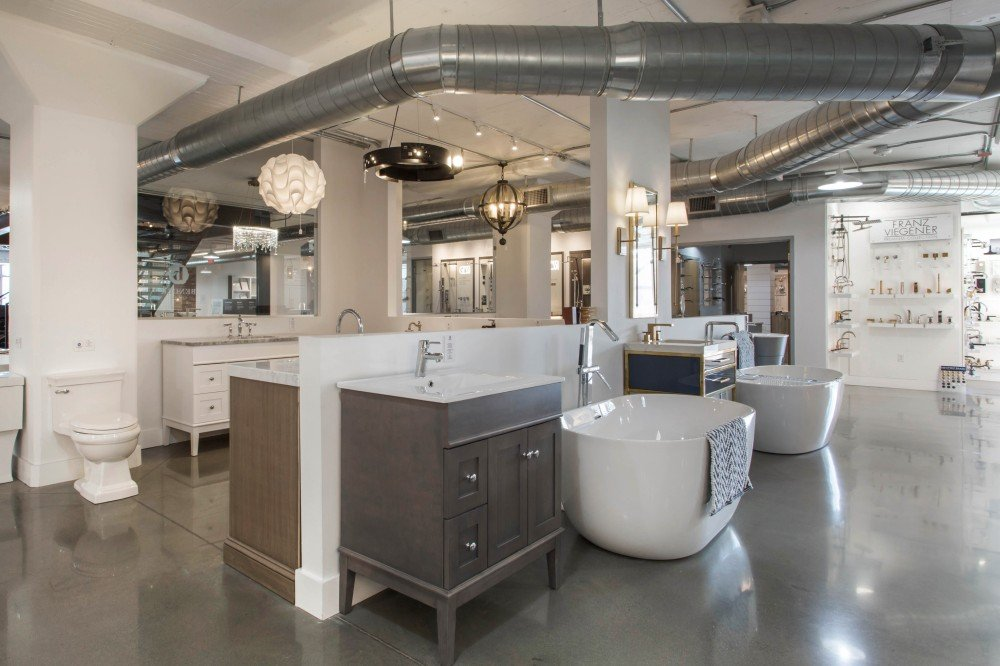 Bender showroom showcasing bathtubs, vanities, toilets, faucets, and lighting