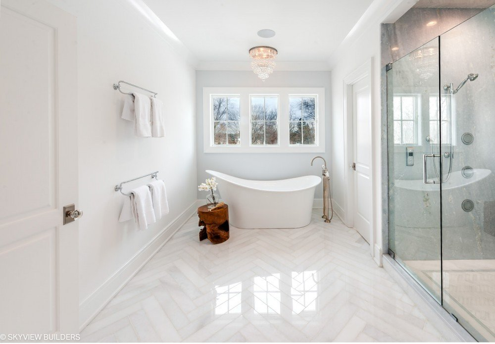 white subway style tile in chevron pattern on bathroom floor