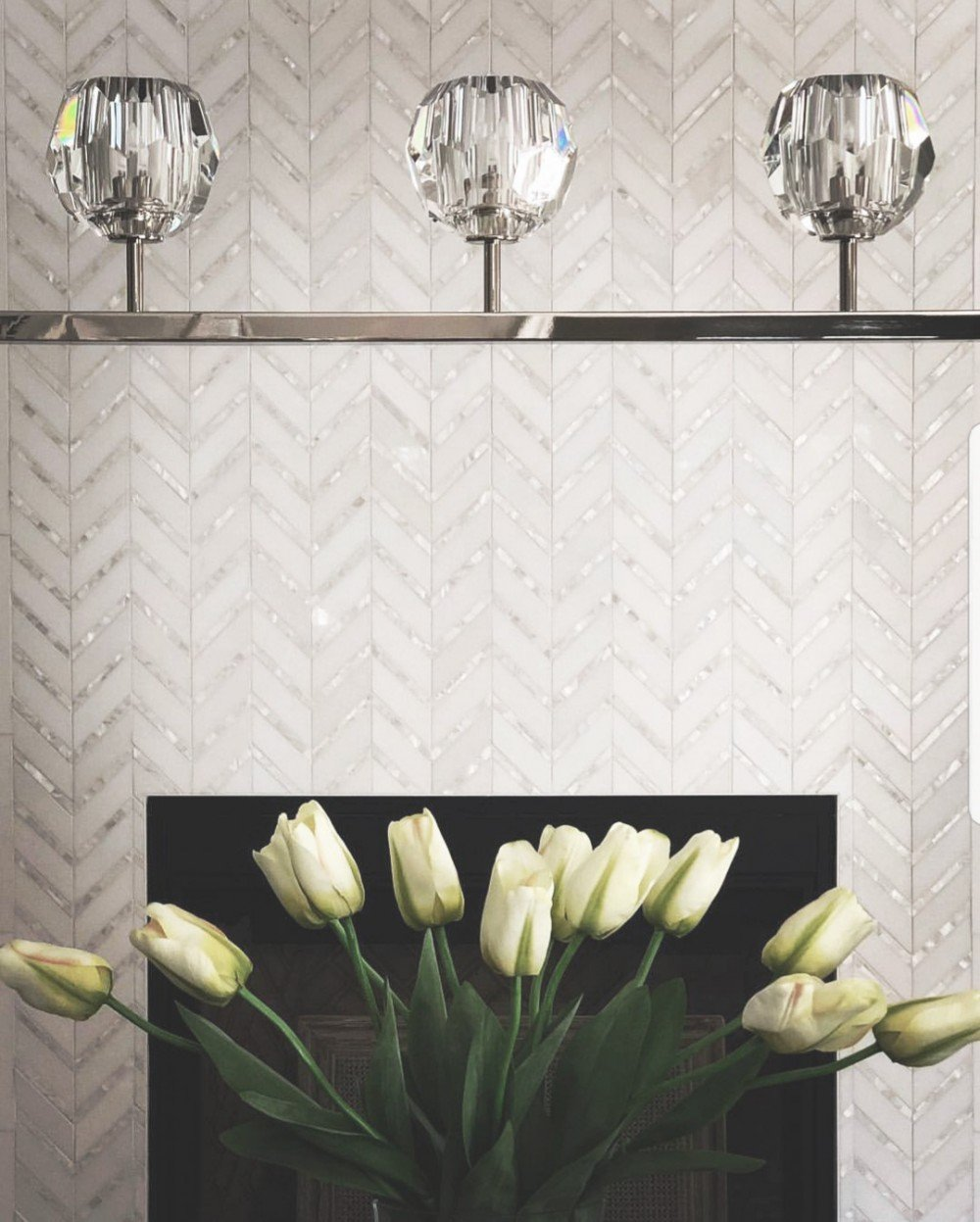 metallic glass tile fireplace surround in chevron pattern
