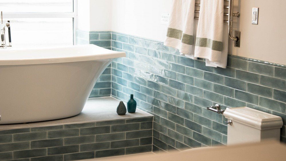 blue subway style tile wall in bathroom