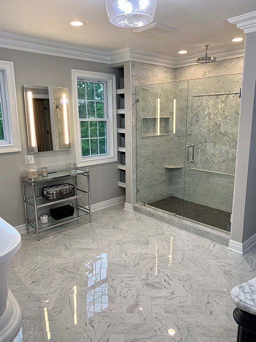 White bathroom remodel with walk in shower, white marbled tile floor, and free standing tub
