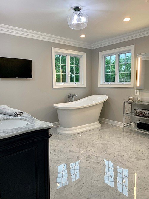 White bathroom remodel with free standing tub and white marbled floors with recessed and flush mount lighting